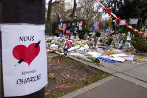 Signs,flags, flowers, candles honoring Ahmed Merabet, Paris policeman