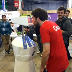 Crew member of Maker Fair using camera mounted on robot to express feelings. Robot's eyes turn to hearts