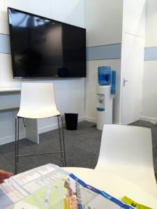 Vacated exhibition stand with TV flat screen, water cooler, chairs, table