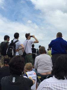 Woman sitting on a folding chair, helicopter in background and man looking through binoculars. Everywhere you look there is a view of something at the Paris Air Show