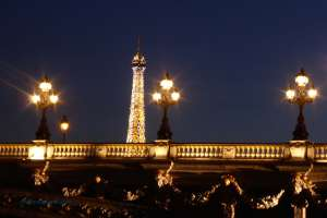 Eiffel Tower as a backdrop of twinkling lights to Pont Alexandre III on a Paris photo night walk capturing movement