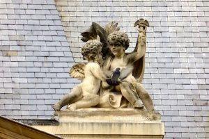 Two angels and a pigeon - all have wings - Angel holding a caduceus, Mercury's emblem for commerce and negotiation; palm leaves behind the cherubs symbolize victory Hôtel de Soubise, Paris