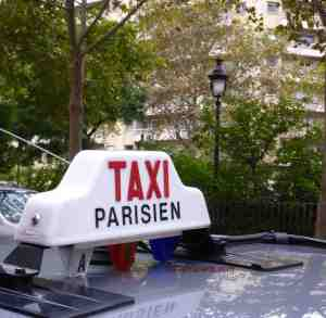 Taxi Parisien sign on top of car