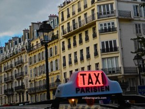 Taxi Parisien sign on top of taxi in the Marais lampost and buildings on rue Saint Antoine