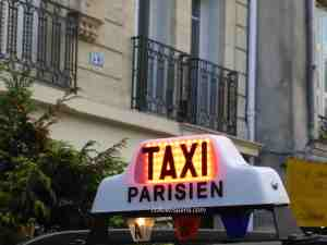 Taxi Parisien sign on top of taxi in the Marais
