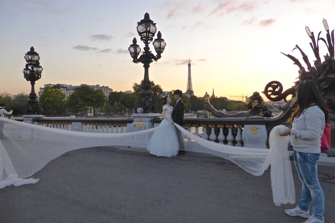 Wedding couple on Pont Alexandre III bridge being photographed at sunset with the Eiffel Tower in the background, girl holding veil, Paris