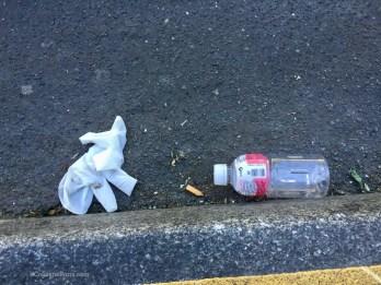 Latex gloves on street and plastic bottle
