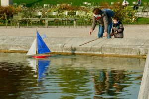 Mother and son at the Luxembourg basin playing with a boat