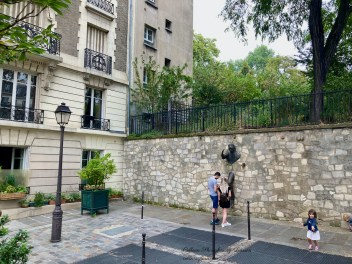 Couple looking at the description of Le Passe-Muraille Place Marcel Aymé