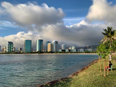 View from a leafy boardwalk across the water of the Honolulu skyline