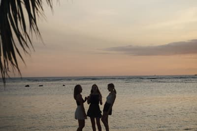 Silhouettes of three female students on the beach just after sunset
