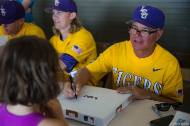 2017 College World Series, Day 1: LSU head coach Paul Mainieri signs an LSU base for a young fan during their team autograph session.