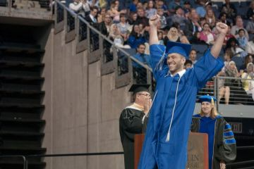 Collin College graduate celebrates as he walks across the stage