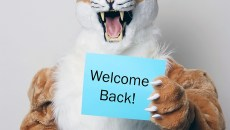Collin Cougar holds Welcome Back sign