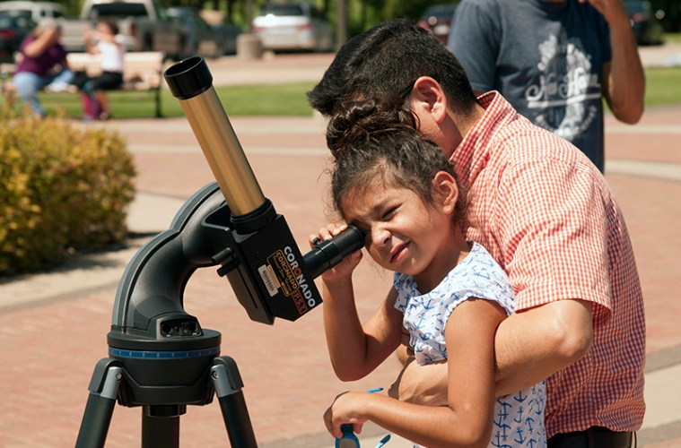 Looking at the solar eclipse through a specialized telescope on Central Park Campus.