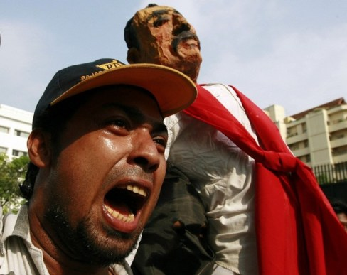 A university student shouts near a puppet of Sri Lanka's President Rajapaksa during a protest in Colombo
