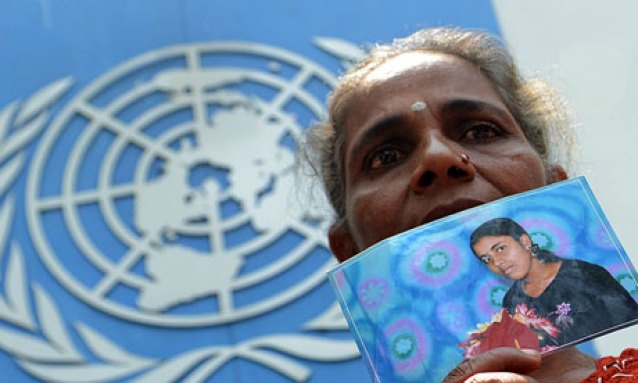 A Sri Lankan Tamil woman holds a portrait of a missing relative