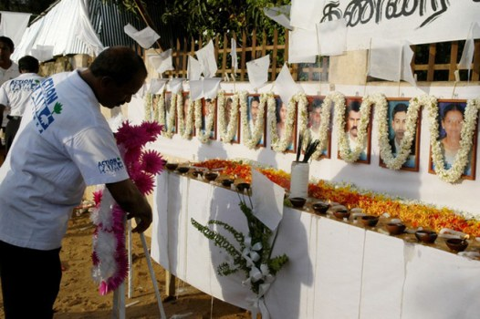 A member of the French aid group Action Contre La Faim places a wreath in front of the photographs of his 17 slain colleagues at their memorial in Batticaloa, Sri Lanka on August 11, 2006