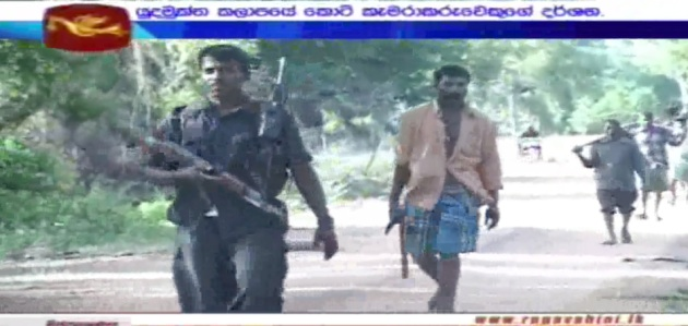 This screenshot shows an unarmed civilian work group lead by an armed, uniformed LTTE cadre – May 2009