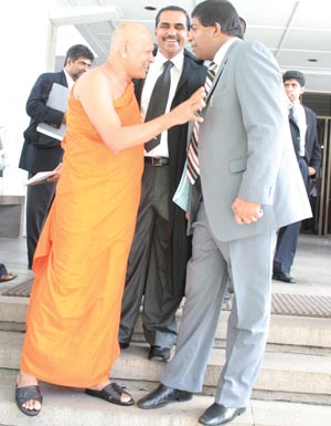 Petitioners Ven. Thiniyawala Palitha Thero and UNP MP Ravi Karunanayake in a jubilant mood outside the Supreme Court Friday following the court order suspending the CPC hedge deal. In the centre is Attorney at Law G.G. Arulpragasam - File photo - November 2008