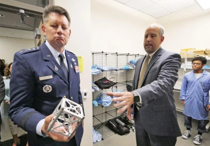 Scott Palo hands General Thompson the framework for a CubeSat