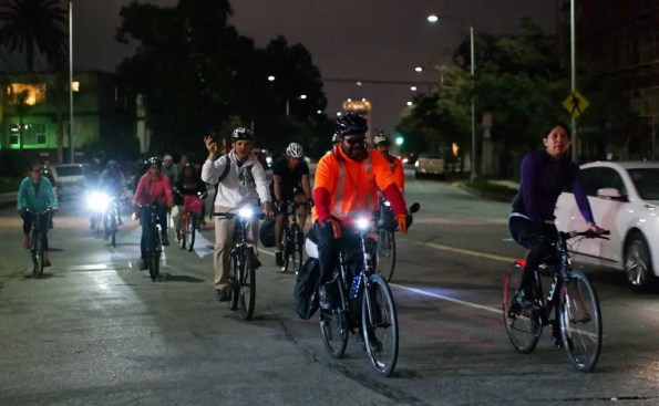 A large group of bikers are biking at night for Taste of Pasadena event