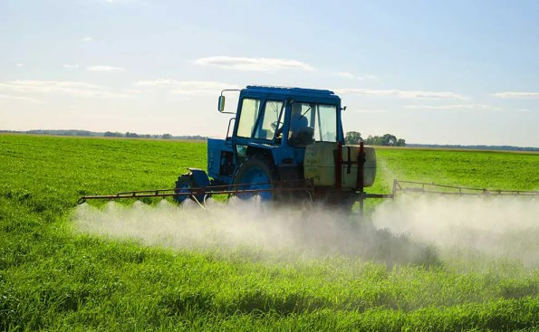 Tractor sprays a field with insecticide (Photo - Aqua Mechanical, flickr).