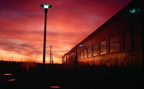 a train passes by in a reddish hue of sunrise