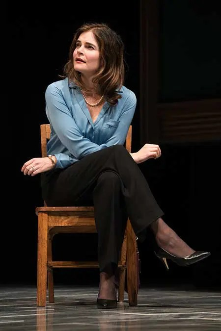 A woman in a blue top and black pants sitting on a chair