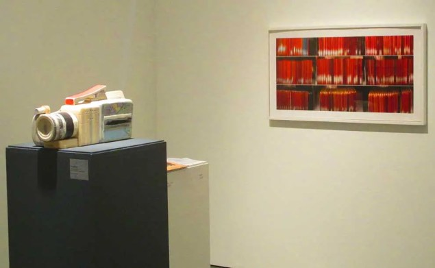 a painting of deep red colors and a stand with a camera made of books