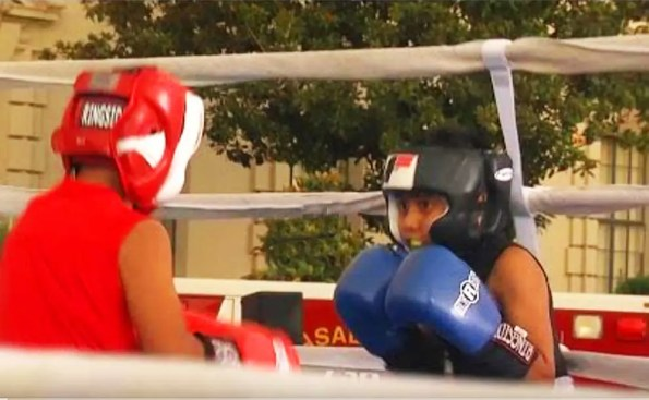 2 kids one wearing red and another wearing blue boxing each other