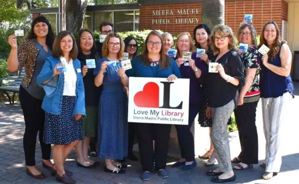 A group of women holding their library card in their hands
