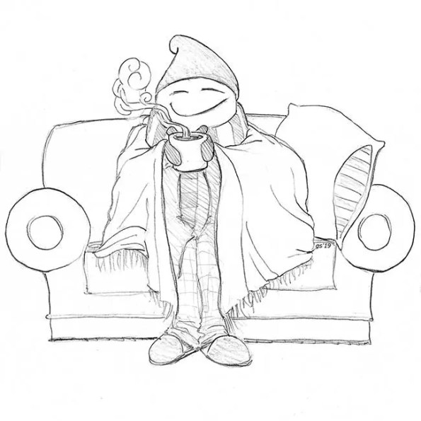 A person with a hot drink and covered with warm clothes sitting on a sofa