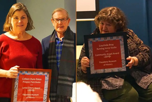 A woman in a red sweater stands near a man with glasses and another woman sitting, both holding a plague honoring them