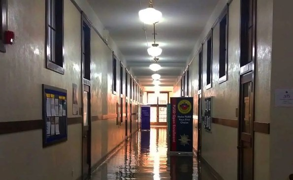 A hallway with lighting fictures in the ceiling and a door with PUSD logo on it