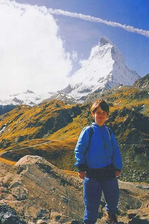 A boy in blue jacket stands in front of the alps