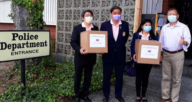 men in suits holding bozes of donations in front of a Police Station