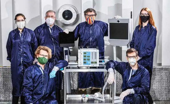 Scientists in blue jump suits gather around a ventilator
