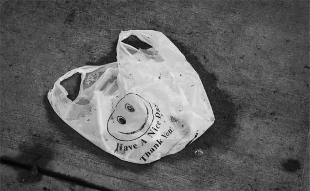 A plastic bag thrown on the sidewalk with the wrods: Have a nice day