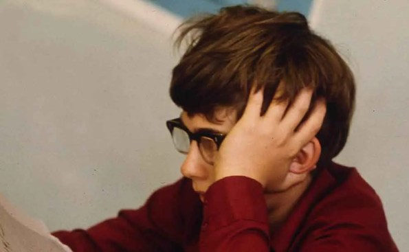 A student with glasses holding his head with his hand