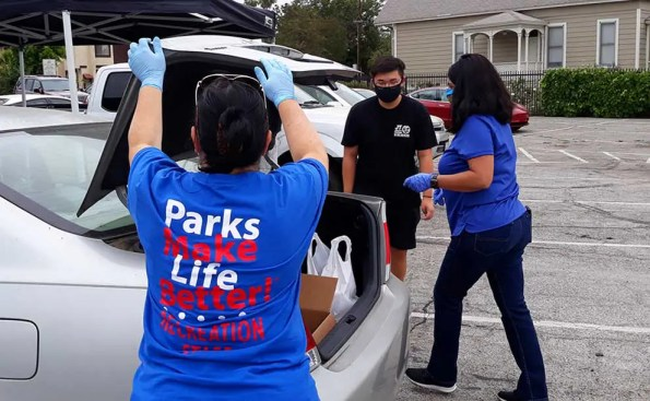people in blue shirts deliver food to the trunk of a car