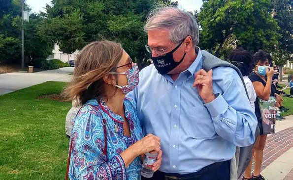 A white haired man with a woman next to him, both with masks