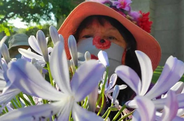 Woman with a hat and a mask hiding behind flowers