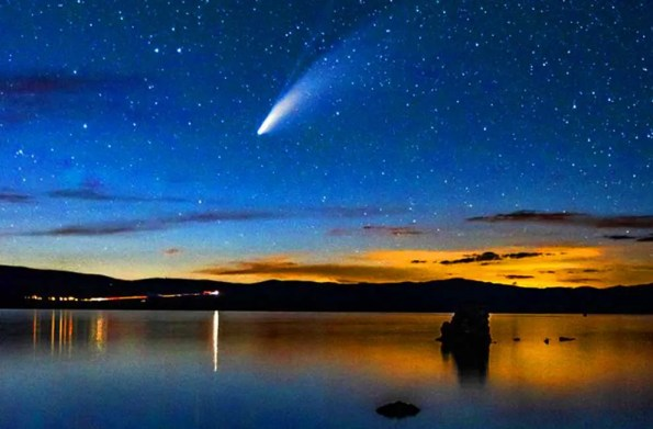 A lake wth a comet above on a clear starry night