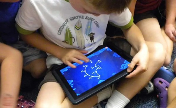 A kid in white shirt playing with a tablet