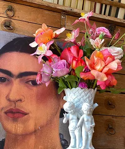 A painting next to a vase full of flowers