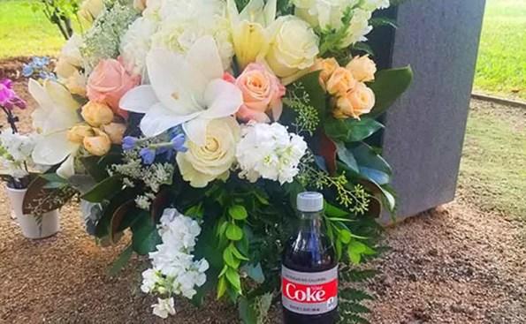 memorial flowers next to a bottle of diet coke