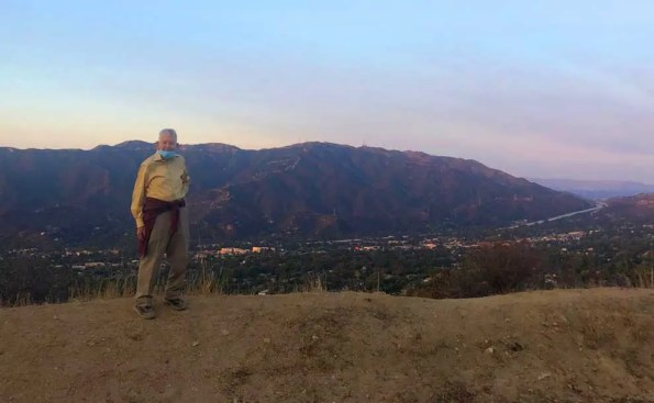 a man in front of mountains and homes at the bottom of the hills
