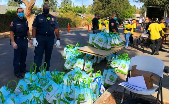 2 police officers next to bags full of giveaway meals