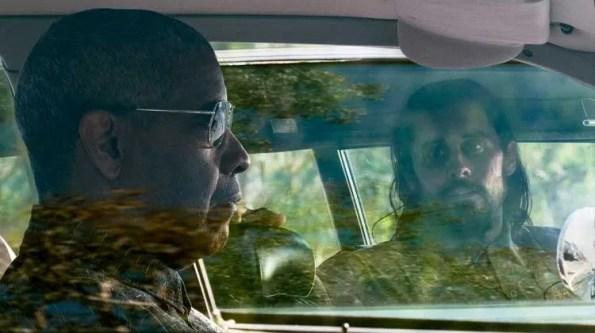 A white man looking at a black man each in their own car